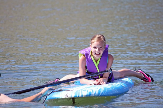 Inexpensive Summer Activities for Kids paddleboarding at the lake State Parks Pass