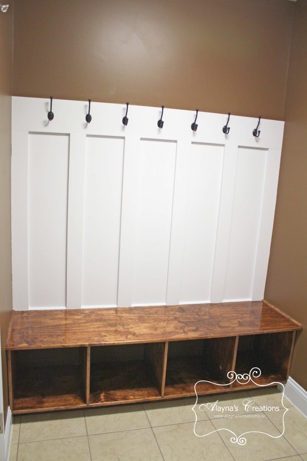 Built ins for mud room entry includes board and batten walls with bench shoe cubbies and hooks for coats and backpacks