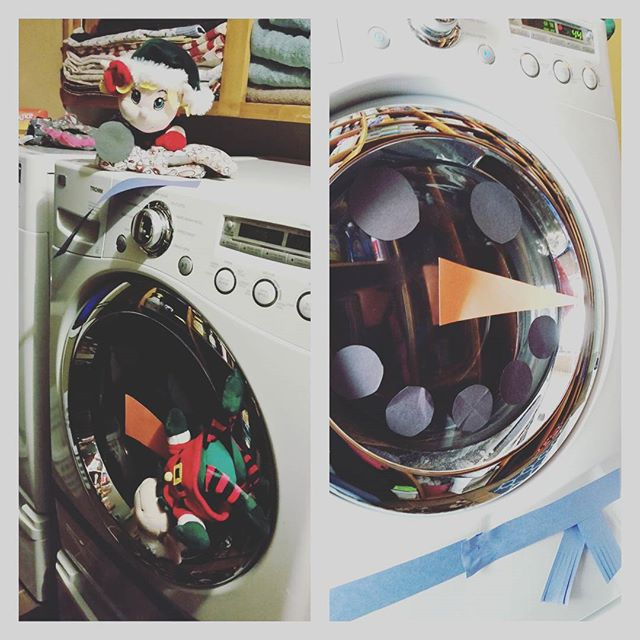 Elf on the Shelf decorating the washer and dryer to look like snowmen